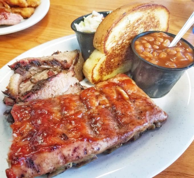 half a rack of ribs, with beef brisket, baked beans, cole slaw and garlic bread on a white plate