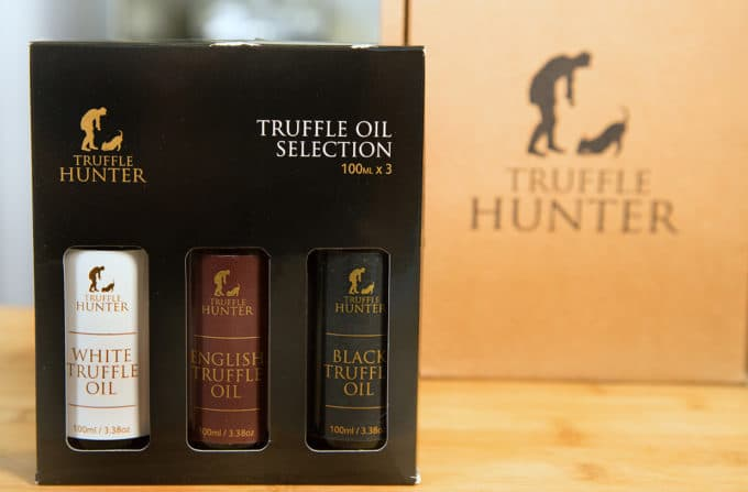 boxed set of thee truffle oils sitting on a cutting board with the shipping box in the background