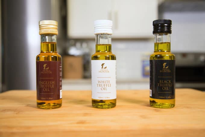 three bottles of truffle oil sitting on a cutting board in a kitchen
