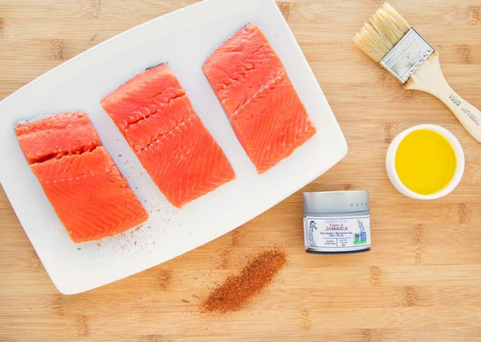 salmon on a white plate, with seasoning, a small bowl of oil and a pastry brush sitting on a cutting board