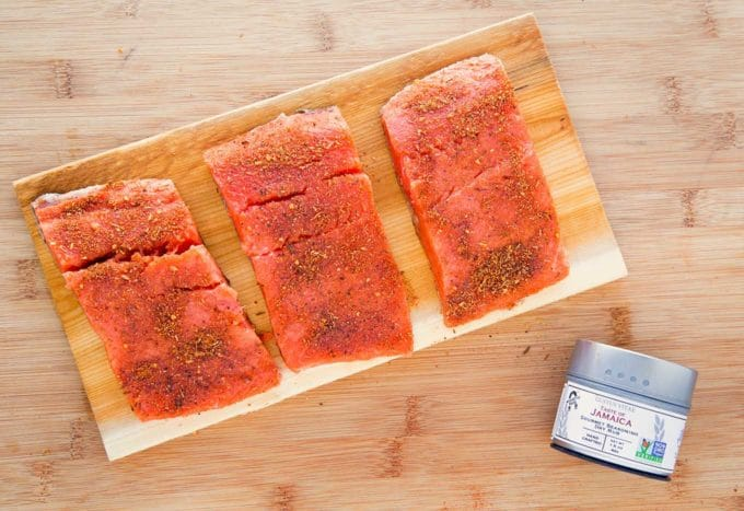 three pieces of seasoned and cooked salmon on a cedar plank sitting on a white plate. with three tins of Gustus Vitae seasonings next to the plate. All sitting on a wooden cutting board
