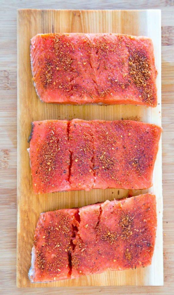 3 pieces of seasoned uncooked salmon on a cedar plank