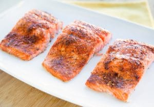 three seasoned and cooked salmon fillets on a white plate sitting on a cutting board