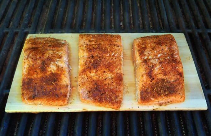 three pieces of seasoned salmon on a cedar plank on a gas grill