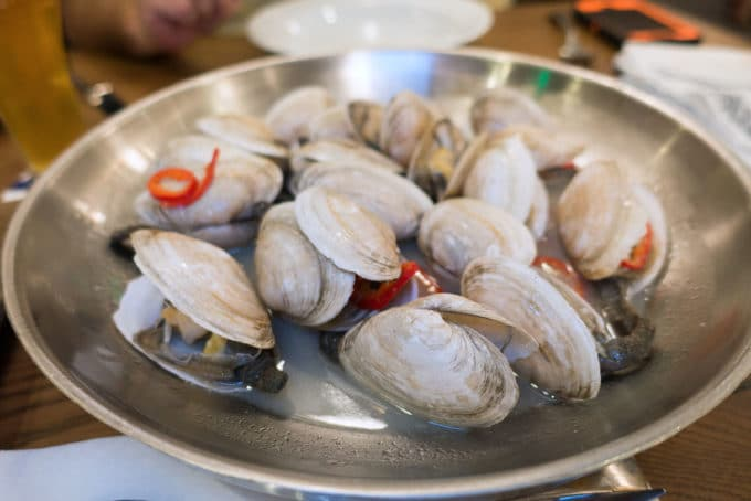 Metal bowl of steamed New England Style Clams in a clam broth with red peppers