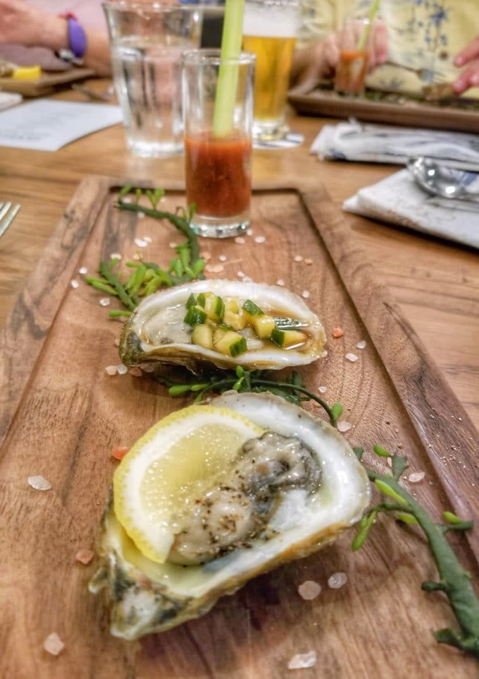 2 oysters on a wooden plank with greens around them and a shooter glass of tomato and and oyster at the end