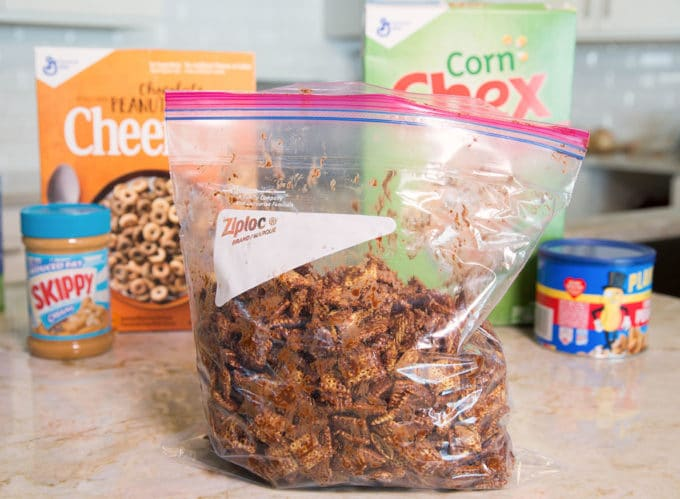 Ziplock bag full of chocolate coated chex cereal with boxes of cereal in the background.