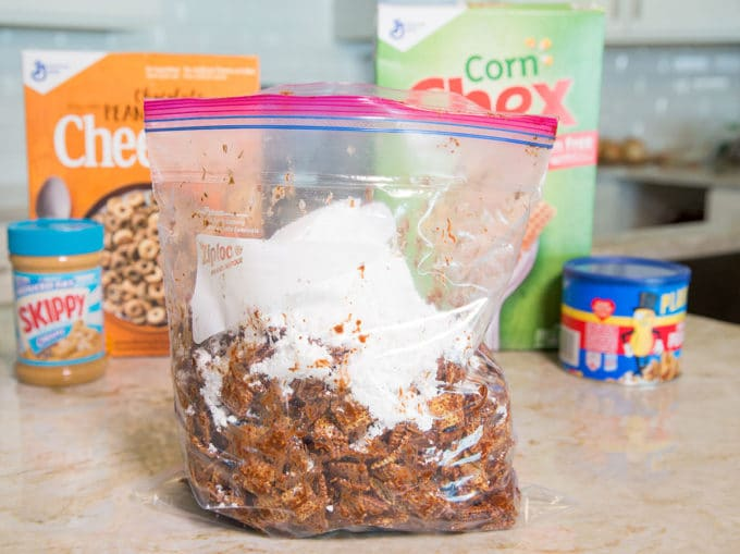 Ziplock bag full of chocolate coated chex cereal and confectioners sugar sitting on a kitchen counter with boxes of cereal in the background.