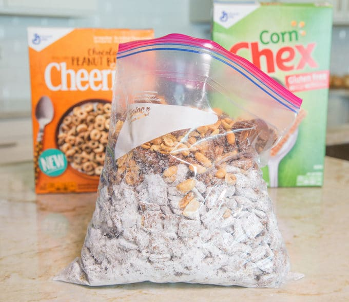 Chex cereal coated in chocolate and confectioners sugar in a ziplock bag with peanuts, peanut butter cups and cheerios sitting on a kitchen counter