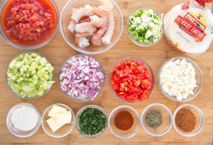 bowls of ingredients to make etouffee street tacos on a wooden cutting board