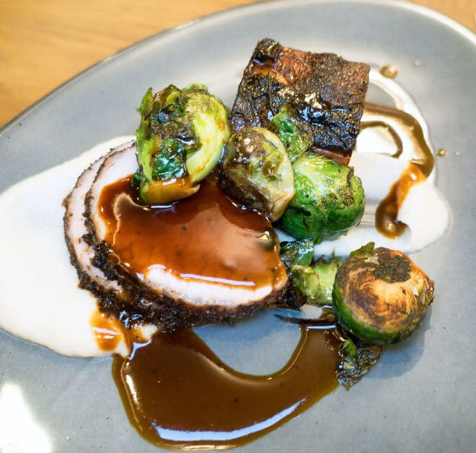 sliced pork loin, and pork belly on top of a pureed cauliflower with seared brussels sprouts and a coffee demi glace over the sliced pork and on the grey plate.