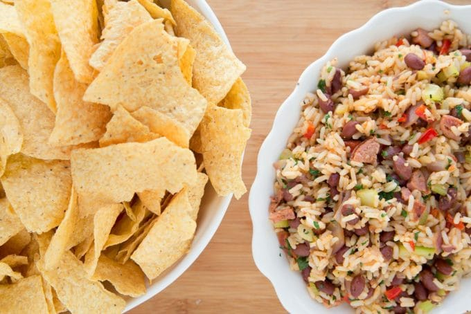 bowl of tortilla chips with a bowl of red beans and rice sitting on a wooden cutting board