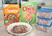 boxes of corn chex and chocolate peanut butter cheerios with Chex Muddy Buddies snack mix in a white bowl and 3 plastic ziplock containers all sitting on a counter top in the kitchen
