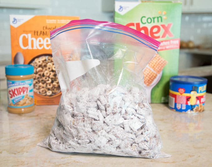 Chex cereal coated in chocolate and confectioners sugar in a ziplock bag sitting on a kitchen counter