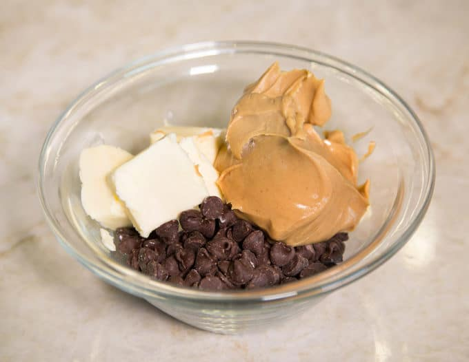semi sweet chocolate chips, peanut butter and butter in a glass bowl on a kitchen counter