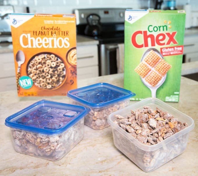 boxes of corn chex and chocolate peanut butter cheerios with Chex Muddy Buddies snack mix in 3 plastic ziplock containers all sitting on a counter top in the kitchen