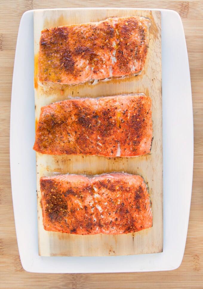 cooked seasoned salmon on a cedar plank on a white platter