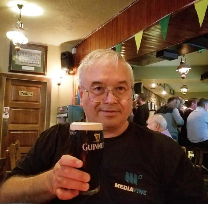 chef Dennis holding a pint of Guinness in a Killarney Pub