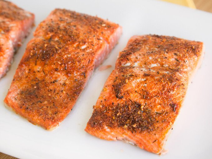 close up of cooked seasoned salmon on a white platter