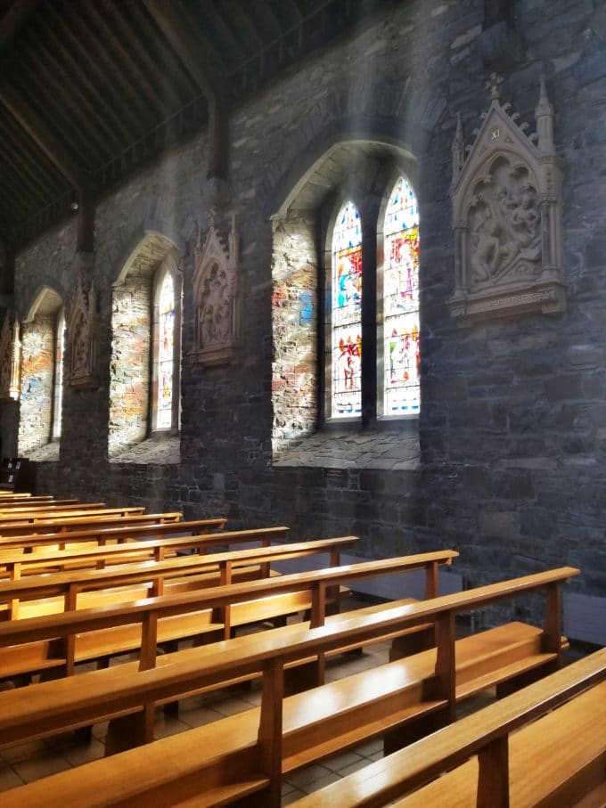 grey stone wall with stained glass windows, light pouring in on wooden peews