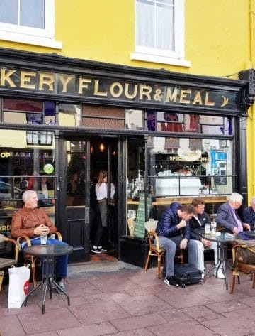 A coffee and pastry shop in Killarney, Ireland with people sitting at tables outside in front of the shop