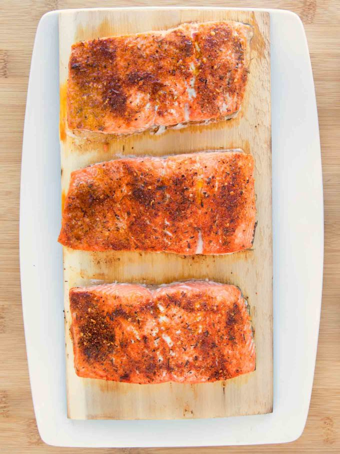three pieces of seasoned and cooked salmon on a cedar plank