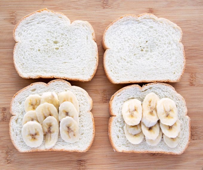 4 slices of thick cut white bread two of which have banana slices on them all sitting on a wooden cutting board