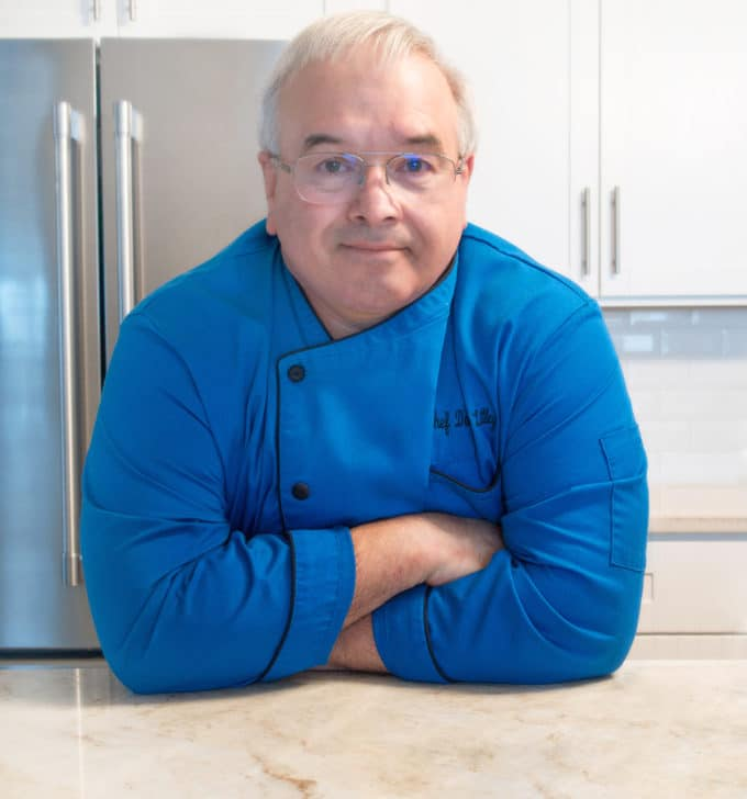 Chef Dennis in a Blue Chef Coat leaning on a kitchen counter with a stainless steel refrigerator and white cabinets in the background