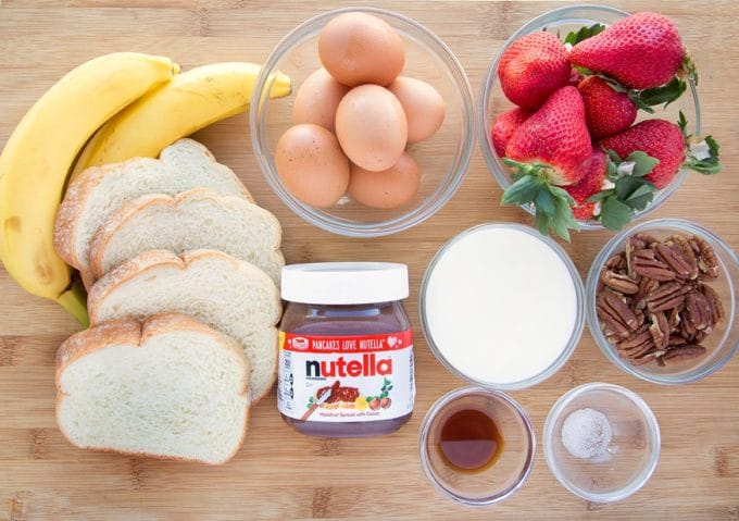 ingredients to make waffle iron banana stuffed french toast with nutella, strawberries and pecans