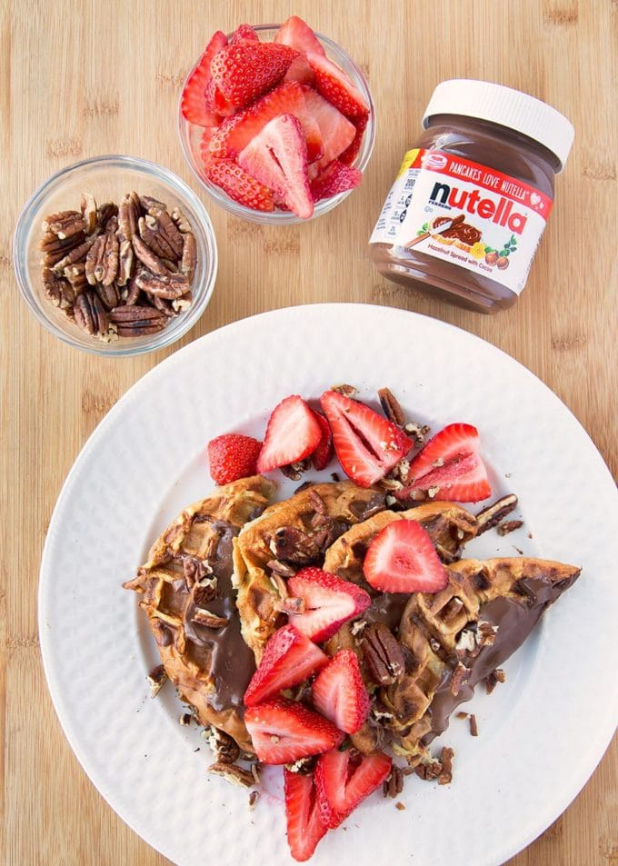 four halves of waffle iron banana stuffed french toast with nutella spread on top with sliced strawberries and toasted pecans all sitting on a white plate on a cutting board with a jar of nutella and bowls of sliced strawberries and pecans