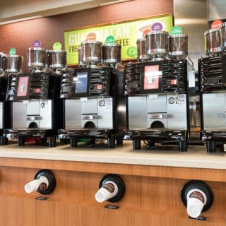 row of three compartment coffee bean grinders and brewers sitting on the counter at RaceTrac