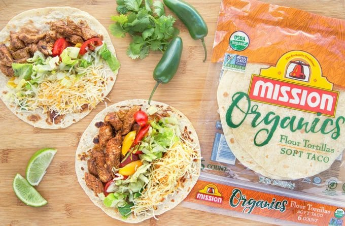 2 flour tortillas filled with blackened chicken strips, shredded lettuce sliced grape tomatoes, and Mexican blended cheese. Sitting on a wooden cutting board with a pack of Mission Organic's Flour Tortillas., lime wedges, jalapenos and cilantro