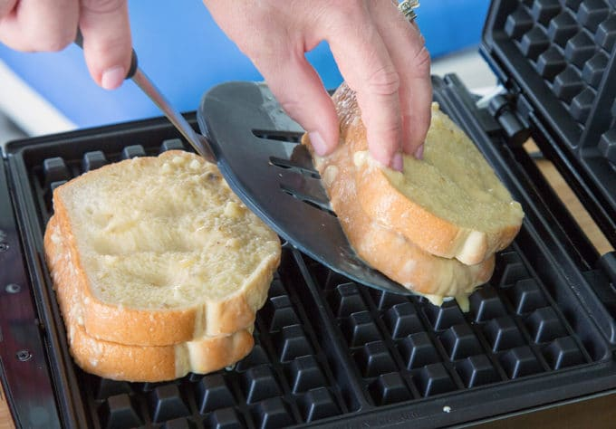 one banana stuffed french toast being placed on a waffle iron in front of another sandwich using a black plastic spatula