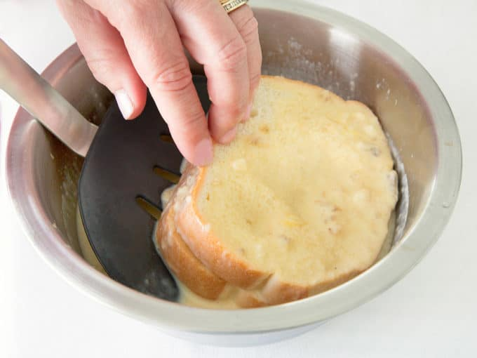 removing dipped french toast sandwich from the egg batter using a black spatula and one hand