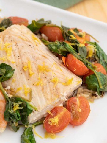 poached mahi-mahi with shrimp on a bed of spinach, tomatoes and rice on a white plate