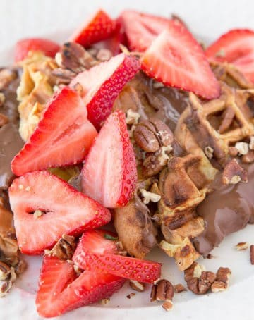 four halves of waffle iron banana stuffed french toast with nutella spread on top with sliced strawberries and toasted pecans all sitting on a white plate