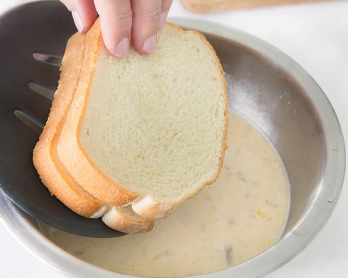 stuffed french toast being lowered into a stainless steel bowl of banana egg batter with a black spatula