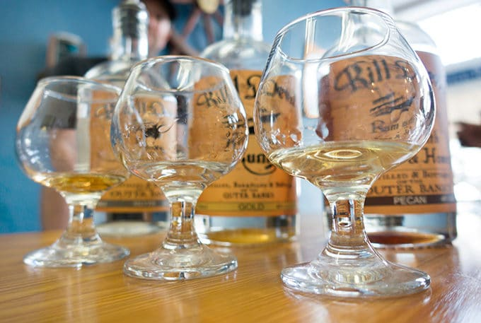 Kill Devil hills Rum poured into three snifters with the bottles behind them