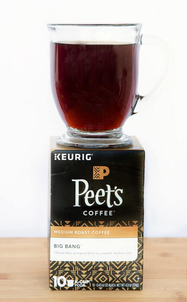 Box of Peet's Coffee K-Cups with a glass mug of black coffee sitting on top of the box