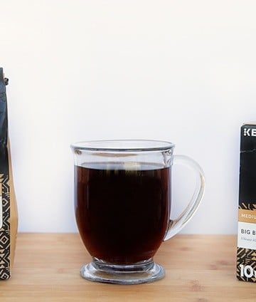 Bag of Peet's Coffee and box of Peet's Coffee K-Cups with a glass mug of black coffee sitting on a cutting board