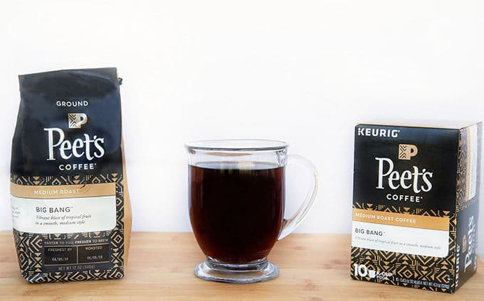 Bag of Peet's Coffee and box of Peet's Coffee K-Cups with a glass mug of black coffee sitting on a cutting board