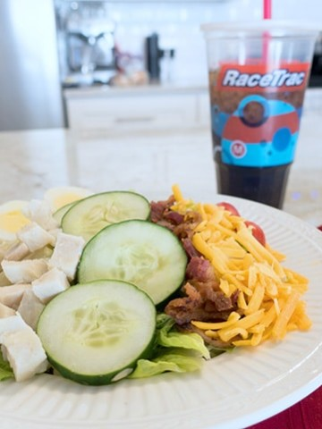 cobb salad in a white bowl sitting on a counter top with a red napkin and silverware and a clear plastic cup of soda with ice