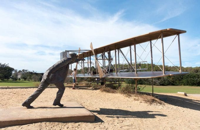 statues of the Wright Brothers and their plane on a sand dune in Kitty Hawk