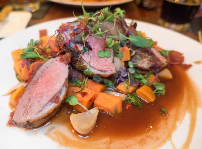 Seared duck breast with vegetables and demi glace on a white plate