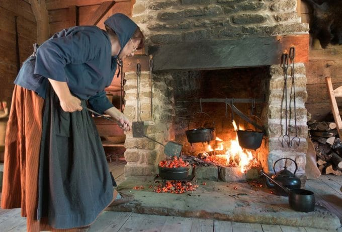 madame savoie placing coals on a dutch oven in front of large fireplace in the Acadian village in Caraquet