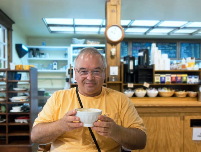 Chef Dennis holding a white bowl of coffee in a coffee shop