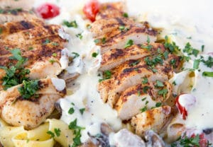slices of seasoned grilled boneless skinless chicken breast sitting on top of Pappardelle with alfredo sauce, grilled cherry tomatoes and mushrooms sprinkled with chopped parsley