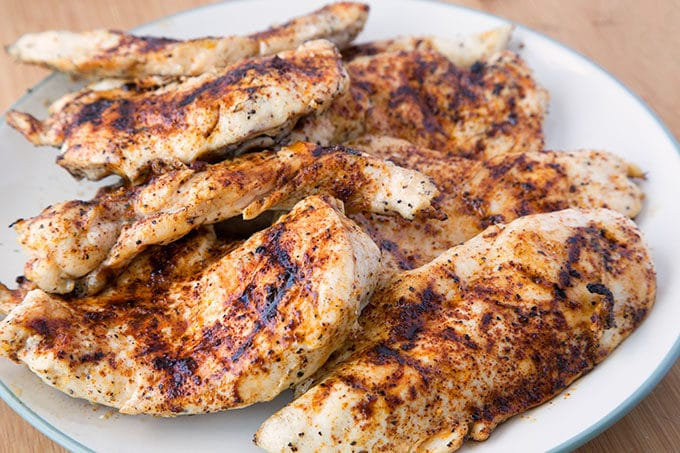 seasoned grilled boneless skinless chicken breasts on a white plate