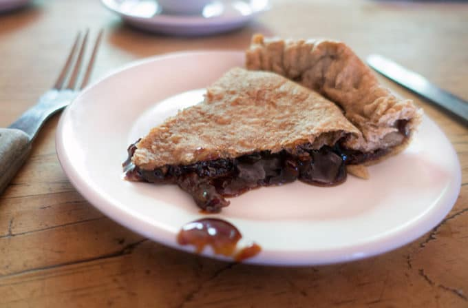 slice of molasses pie on a white plate sitting on a wooden table with a knife and fork along side