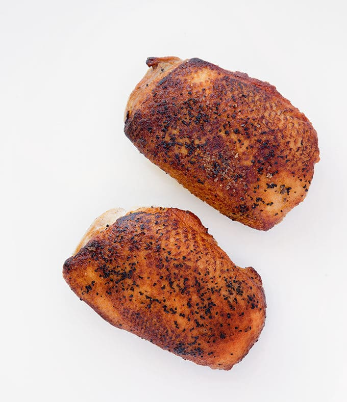 2 dark golden brown pan seared duck breasts seasoned with salt and pepper on a white plate